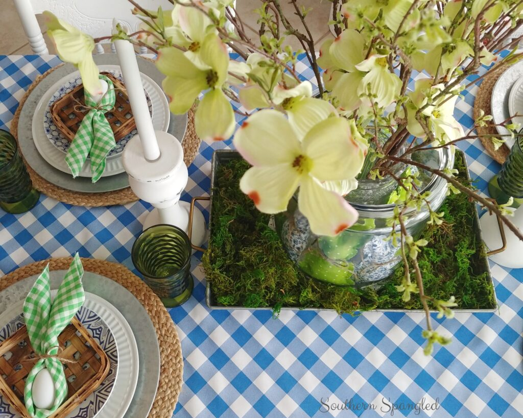 Blue and green Easter table setting with bunny napkin folds, layered place settings, and dogwood stems