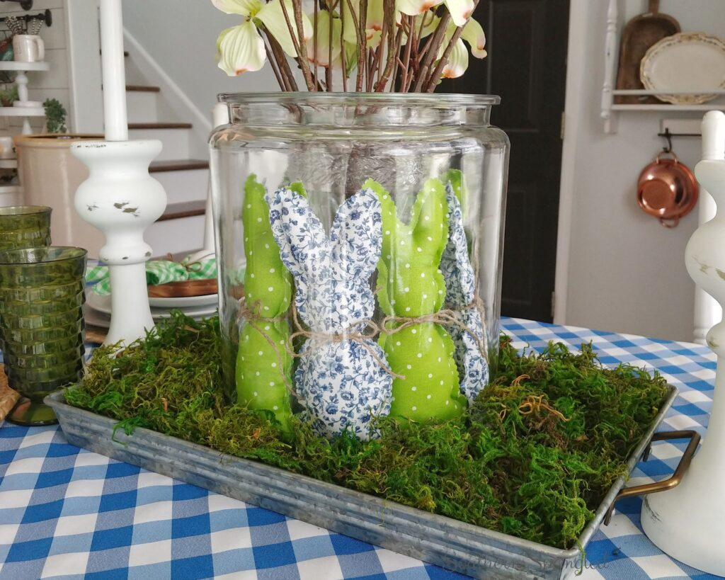 Blue and green Easter bunny centerpiece in glass container with real moss