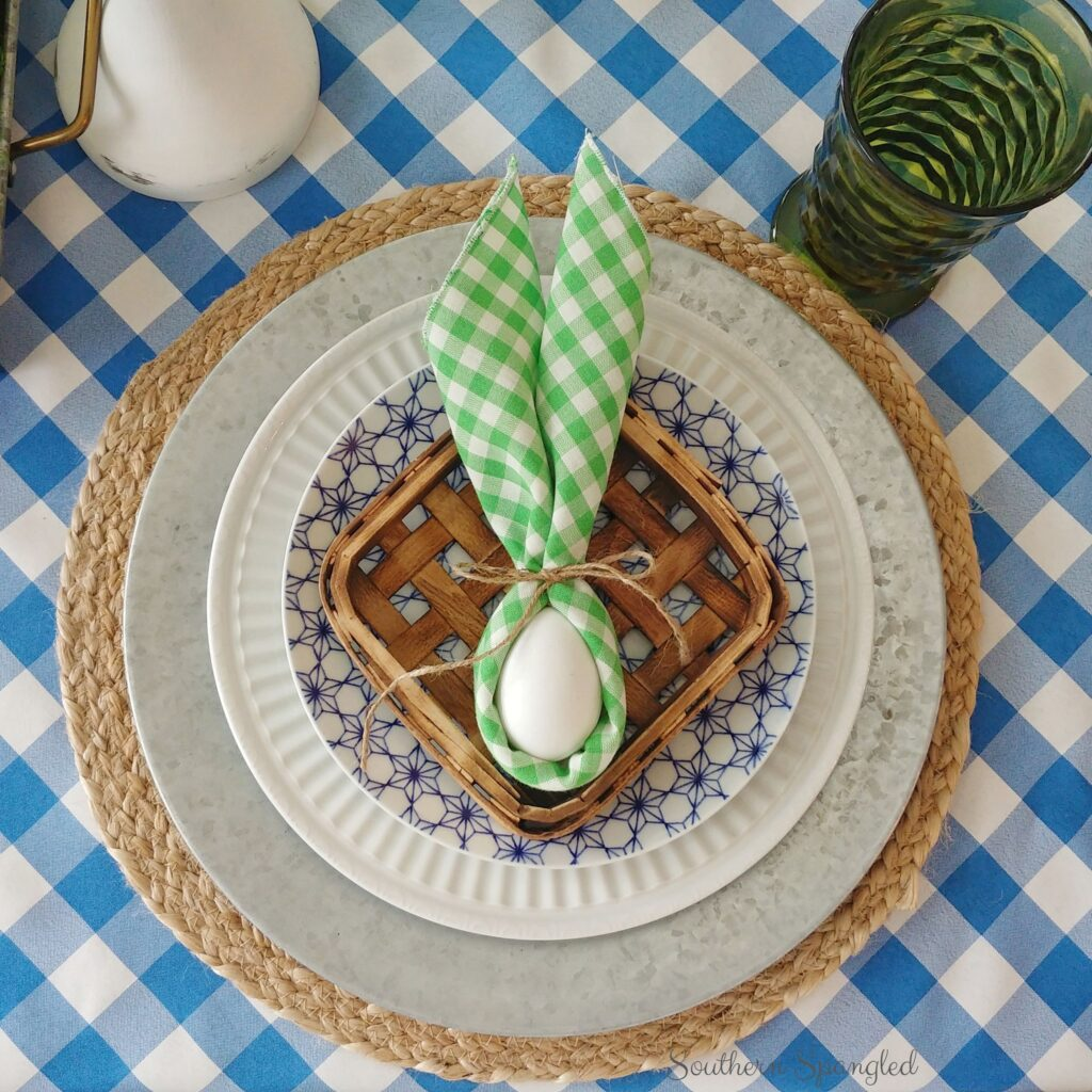 Farmhouse Easter place setting with layered placemat, galvanized charger, dishes, tobacco basket, and bunny ear napkin