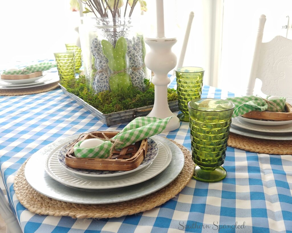 Blue and green Easter table decor with bunnies and vintage glassware.